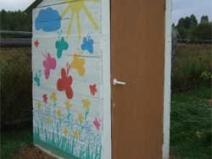 Простой туалет на даче можно раскрасить яркими красками