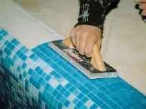 Процесс фиксации мозаики на стенке бассейна